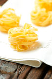 Nests of dry pasta on tablecloth. Nests of dry pasta tagliatelle on white table cloth royalty free stock images