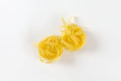 Nests of dry pasta tagliatelle Stock Photo