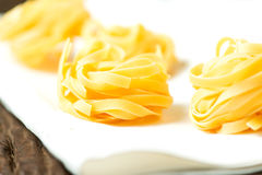 Nests of dry pasta tagliatelle on tablecloth horizontal. Nests of dry pasta tagliatelle on white table cloth stock photos