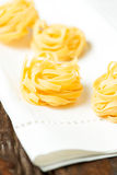 Nests of dry pasta tagliatelle on tablecloth vertical macro. Nests of dry pasta tagliatelle on white table cloth stock photo