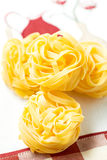 Nests of dry pasta tagliatelle on tablecloth vertical and red. Nests of dry pasta tagliatelle on white table cloth royalty free stock photo