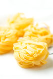 Nests of dry pasta tagliatelle on tablecloth vertical. Nests of dry pasta tagliatelle on white table cloth royalty free stock image