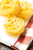 Nests of dry pasta tagliatelle vertical. Nests of dry pasta tagliatelle on white table cloth stock images