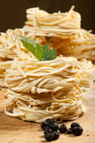 Nests of dry pasta. On wooden table Royalty Free Stock Photos