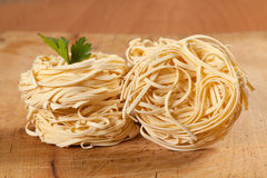 Nests of dry pasta. On wooden table Stock Image