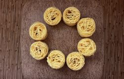 Nests of pasta on a brown background. Round frame from nests of pasta on a brown background royalty free stock images