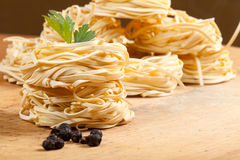 Nests of pasta. Nests of dry pasta on wooden table Royalty Free Stock Photo