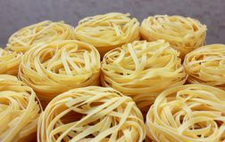 Nests of pasta on gray background. Several round nests of pasta on gray background royalty free stock photos