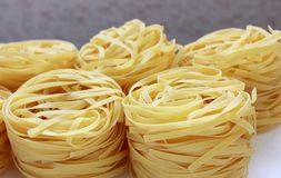 Nests of pasta on gray background. Several round nests of pasta on gray background stock photo
