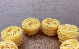 Nests of pasta on gray and brown background. Several round nests of pasta on gray and brown background stock photo