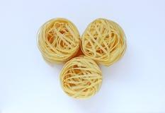 Nests of pasta on white background. Three nests of pasta on white background stock photography