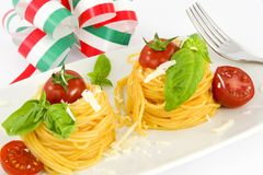Nests of spaghetti con tomato and basil. Traditional Italian dish, spaghetti with Italian Royalty Free Stock Image