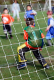 In the Net. The net of a soccer goal with the goal keeper and other young players in the blurred in background Stock Images