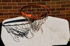 Upside down basketball backboard. The net of a basketball hoop is shadowed against the white backboard which tis hung upside down Stock Image