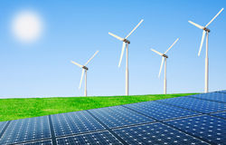 Net energy of the sun and wind. Wind turbines and solar panels in field Royalty Free Stock Photos