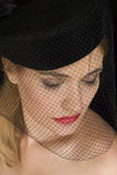 Net face. Attractive cabaret girl looking down with a hat and net over her face Stock Images