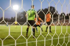 Net in a football goal. With playrs and pitch in the background royalty free stock image