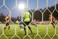 Net in a football goal. With playrs and pitch in the background stock image