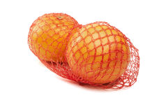 Net with fresh grapefruits on white background Royalty Free Stock Photography