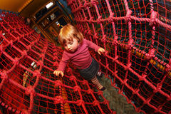 Through the net maze. Little girl having fun on an indoor playground in an activity centre stock image