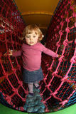 Through the net maze. Little girl having fun on an indoor playground in an activity centre royalty free stock images