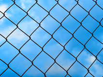 Net metallic barrier against blue sky Royalty Free Stock Photos
