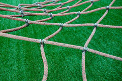 Net over astroturf. Climbing net hanging over astroturf in playground Royalty Free Stock Photography