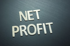 Net profit written with wooden letters on a green background Royalty Free Stock Images