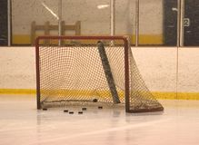 Net with pucks. Hockey goal filling with pucks during warm up before a hockey game Royalty Free Stock Photos