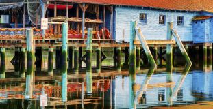 A net shed reflects in the Puget Sound at Gig Harbor. A netshed reflects in the still waters of the Puget Sound in Gig Harbor, Washington Stock Photos