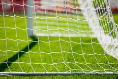 Net of a soccer goal. Football grass pitch. Net of a soccer goal. Soccer or football goal net. Football grass pitch on a sunny day. Sports soccer background Stock Photo