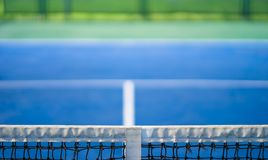 Net of tennis with white stripe in blurred blue and green court, competition concept Stock Photography