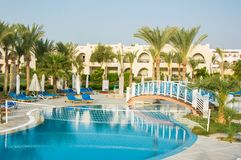 Net for water volleyball over the swimming pool at the resort. E. Mpty loungers near the swimming pool at the hotel in Egypt stock photography