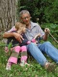 Neta abraçada com avô Fotografia de Stock