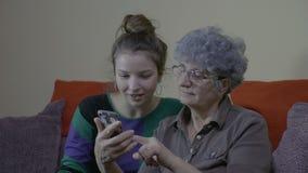 Neta acolhedor que olha sua avó que usa um smartphone que ri e que tem uma boa estadia na sala de visitas vídeos de arquivo