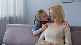 Neta bonito que dá o presente à avó e que abraça a, amor da família video estoque
