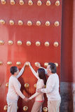 Neta com as avós que estão ao lado das portas vermelhas tradicionais e que guardaram as mãos Fotografia de Stock