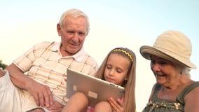 Neta com tabuleta do PC e a avó surpreendida video estoque
