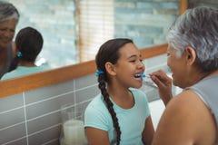 Neta de ajuda da avó para escovar seus dentes no banheiro foto de stock royalty free