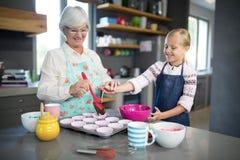 Neta de ajuda de sorriso da avó ao derramar a massa do queque fotografia de stock