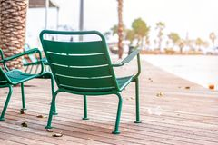 15/12/2018 Netanya, Israel, iron street chairs for passersby are chained to the waterfront on a warm winter stock photography