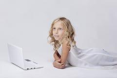 有netbook的,白色背景美丽的白肤金发的小女孩 库存照片
