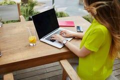 在netbook键入的文本的年轻女商人工作在现代咖啡店的早餐期间 库存照片