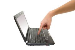 Netbook. Finger touching keyboard of black netbook stock photography