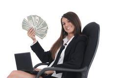 Netbook e dinheiro do witn da menina na cadeira imagens de stock
