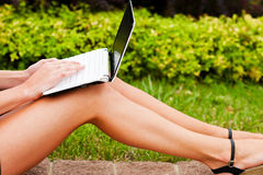 Netbook tanned legs. Business woman working with laptop on lap Royalty Free Stock Photography