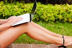 Netbook tanned os pés fotografia de stock royalty free