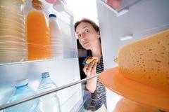 Netelig meisje die zoete cake houden en koelkast onderzoeken royalty-vrije stock foto