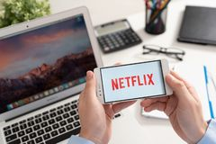 Netflix is a global provider of streaming movies and TV series. Wroclaw, Poland - JAN 31, 2019: Man holding smartphone with Netflix logo. Netflix is a global royalty free stock photos