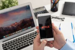 Netflix is a global provider of streaming movies and TV series. Wroclaw, Poland - JAN 31, 2019: Man holding smartphone with Netflix logo. Netflix is a global stock photo